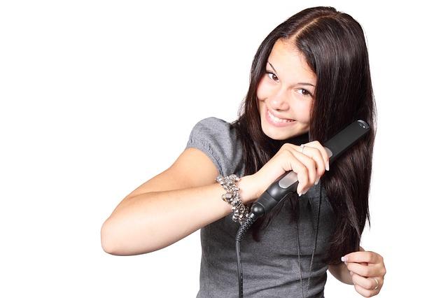 dívka se žehličkou na vlasy