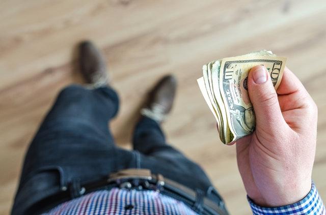 muž držící dolarové bankovky.jpg